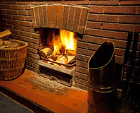 A cosy roaring log fire. Cosy bright Roaring log fire with brick surround glowing with flames going up chimney Stock Image