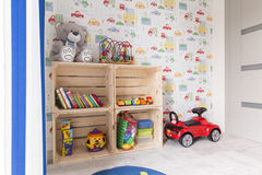 Cosy room with many toys for boys. Light and cosy bedroom with teddy bear, toy cars and colourful wall paper royalty free stock images