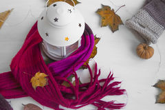 Cosy scarf with candle lantern,dried leaves and pumpkin decorati Royalty Free Stock Image