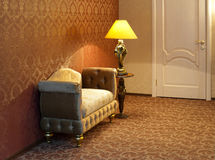 Cosy sofa. A plush settee with a fancy stand lamp Stock Images