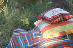 Cosy things for holiday. Knitted and embroidered pillows and striped plaid Stock Image