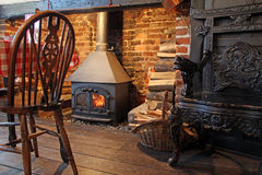 Cosy tudor stove fire burner. Photo of a cosy tudor style restaurant with a stove wood fire burning in fireplace royalty free stock photo