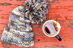 Cosy winter hat with a cup of fresh hot tea Stock Image
