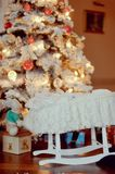 Cot under the Christmas tree Royalty Free Stock Images