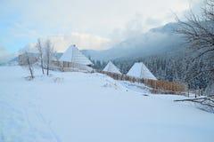 Cotagge onder de sneeuw, door houten omheining wordt omringd die Royalty-vrije Stock Afbeelding