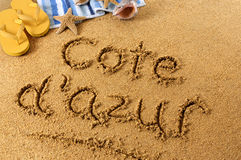 Cote d'Azur beach writing. The words Cote d'Azur written on a sandy beach with towel, starfish and flip flops Royalty Free Stock Photo