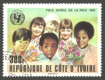 Children with flowers and UNICEF emblem. Cote d`Ivoire - stamp printed in1978, Series Winners of the Nobel Prize, Children with flowers and UNICEF emblem Royalty Free Stock Images