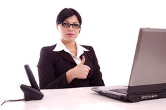 Cotent business woman sitting at her desk. Portrait of a content beautiful business woman  showing the perfect sign sitting at her desk isolated over white Stock Image