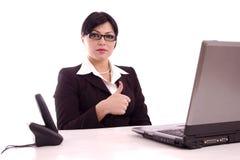 Cotent Geschäftsfrau, die an ihrem Schreibtisch sitzt Stockbild