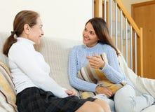 Cotilleo de la hija y de la madre en el sofá Foto de archivo libre de regalías