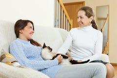 Cotilleo de la hija y de la madre en el sofá Foto de archivo