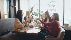 Cotilleo por el cóctel cuatro mujeres jovenes atractivas que beben los cócteles en alameda de compras y que tienen una charla con almacen de metraje de vídeo