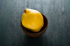 Cotogna gialla in ciotola di legno marrone sulla tavola scura Fotografia Stock