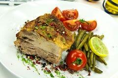 Cotoletta arrostita del porco con l'insalata del pomodoro Fotografie Stock Libere da Diritti