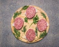 Cotoletta casalinga di manzo per gli hamburger, cerchio allineato su un prezzemolo di legno rotondo del tagliere ed aneto e spezi Fotografia Stock