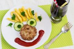 Cotoletta, cetriolo e patate fritte in fronti allegri Children Fotografie Stock Libere da Diritti