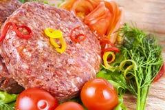 Cotoletta cruda fresca dell'hamburger con le erbe ed i pomodori Fotografia Stock