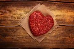 Cotoletta a forma di dell'hamburger del cuore crudo fotografie stock