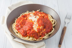 Cotoletta impanata casalinga in salsa al pomodoro e formaggio fuso sopra lo spagetti Fotografia Stock Libera da Diritti