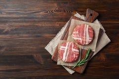 Cotolette crude dell'hamburger con i rosmarini sul tagliere e sulla tavola di legno fotografia stock