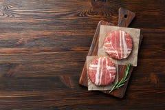 Cotolette crude dell'hamburger con i rosmarini sul tagliere e sulla tavola di legno immagine stock