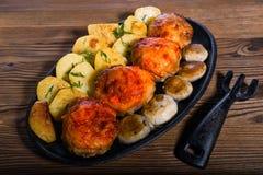 Cotolette del pollo con le fette arrostite dei funghi e delle patate in una vecchia padella Immagini Stock