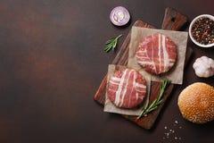 Cotolette, lattuga, panino e cipolla crudi degli ingredienti dell'hamburger su fondo arrugginito immagini stock