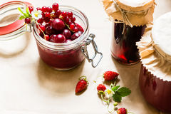 Cotos de la fruta y fresas, cerezas y bayas crudas de las pasas rojas en una tabla de cocina Fotos de archivo