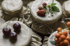 Cotos y fresas crudas, cerezas, bayas de la fruta de serbales en tarros Foto de archivo libre de regalías
