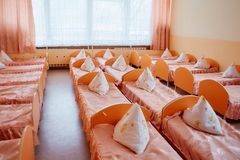 Cots in the kindergarten. Orphanage or boarding school. Beds in a boarding school or in an orphanage royalty free stock image