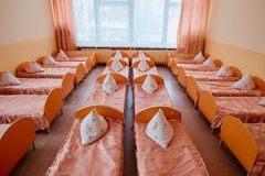 Cots in the kindergarten. Orphanage or boarding school. Beds in a boarding school or in an orphanage stock image
