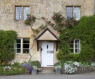 Cotswold cottage facade with flower border Stock Photo