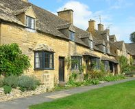 Cotswold cottages. Row of honey coloured, terraced, bay windowed, cottages in the cotswold's Stock Photo