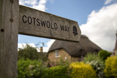Cotswolds  Way. Cotswolds Way sign with thatched house in background - England Stock Photos