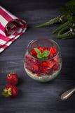 Cotta italiano hecho en casa del panna del postre con las fresas y la menta frescas en un fondo de madera oscuro Fotografía de archivo libre de regalías