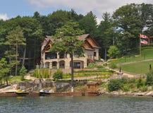Cottage à la maison dans mille îles avec les drapeaux canadiens et américains Images libres de droits
