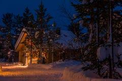 Cottage acceso nella foresta di notte di Snowy fotografie stock libere da diritti
