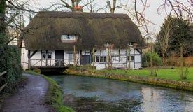Cottage anglais de moulin avec le toit couvert de chaume construit au-dessus d'une rivière photos libres de droits