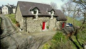 Cottage avec la porte rouge Photo stock