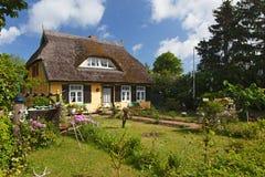 Cottage avec le toit couvert de chaume et le joli jardin Photographie stock libre de droits