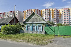 Cottage on the background of high-rise buildings Royalty Free Stock Photography