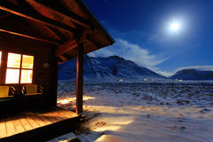 Cottage on a background of mountains in the moonlight. Stock Image