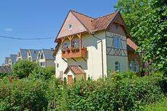 Cottage with a balcony in summer day. Settlement Amber, Kaliningrad region.  Royalty Free Stock Photo