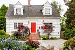 Cottage blanc avec la porte rouge dans le Canada Photo stock