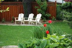 Cottage Chairs. 3 cottage / adarondack chairs in white with tulip and hosta up front royalty free stock photo