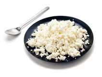 Cottage cheese. On a black round plate isolated Stock Photos