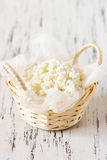Cottage cheese. Fresh farm cottage cheese with cheesecloth in a wicker basket on a wooden background Royalty Free Stock Images