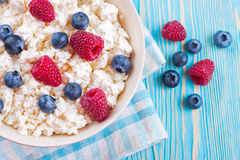 Cottage cheese with berries. Cottage cheese with raspberries and blueberries in bowl on blue wooden background Royalty Free Stock Photography