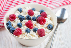 Cottage cheese with berries. Cottage cheese with raspberries and blueberries in a bowl on white wooden background Stock Image