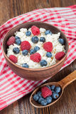 Cottage cheese with berries. Cottage cheese with raspberries and blueberries in brown clay bowl and wooden spoon on red checkered towel Stock Photos